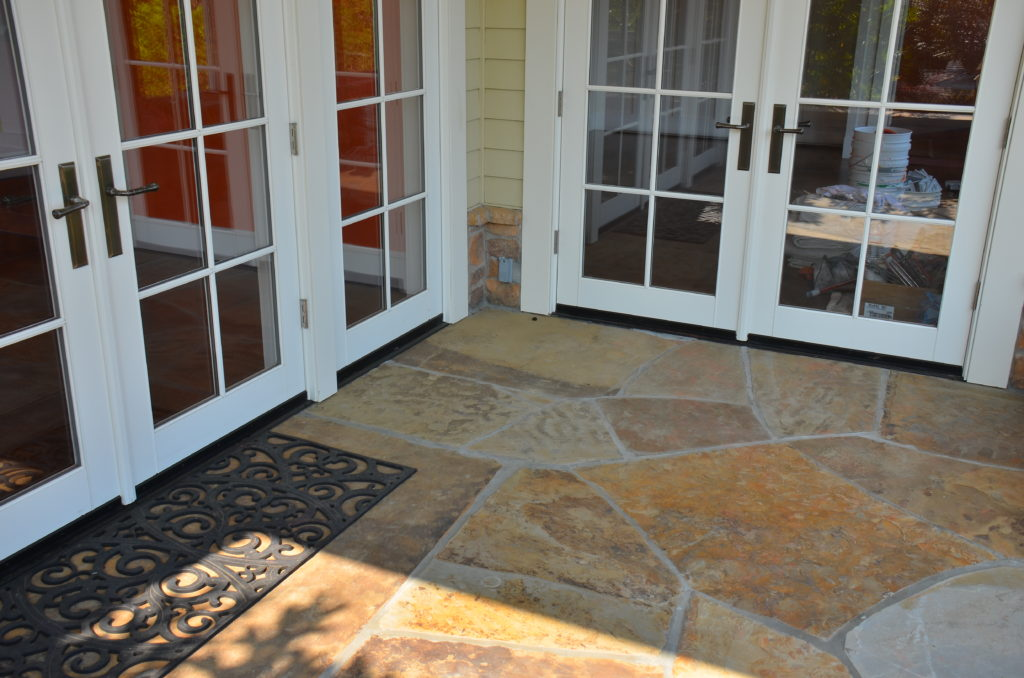 Image of white painted French doors and flagstone patio