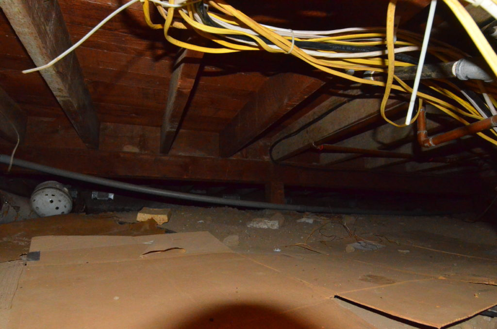 Image of crawlspace area showing dangling wires, debris, framing and exposed dirt