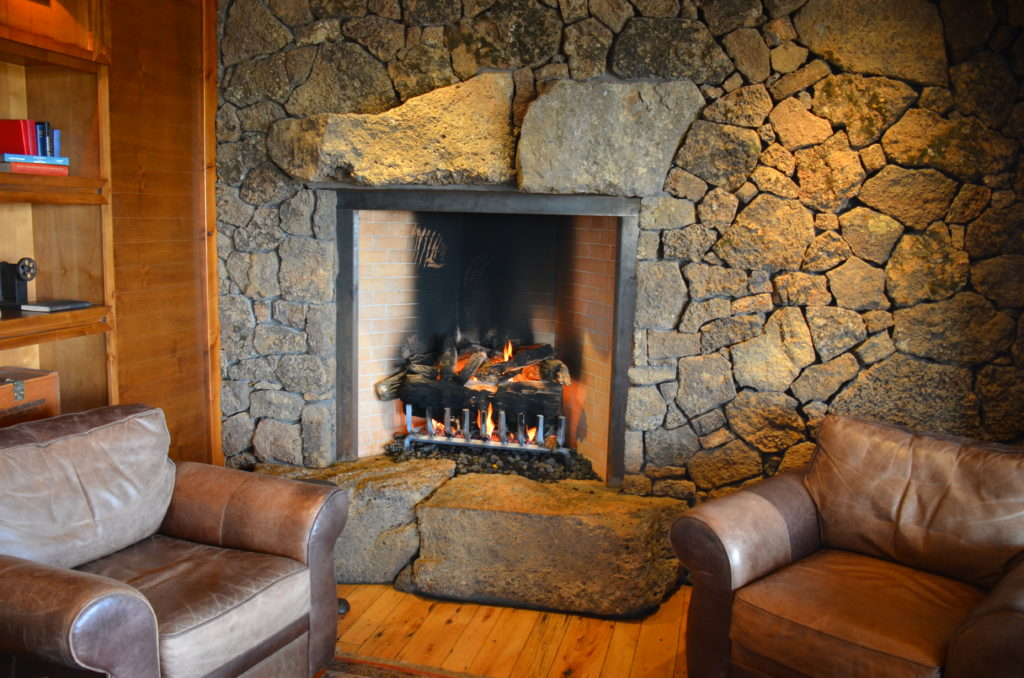image of a rustic stone wood burning fireplace in a living room with nice interior finishes, wood floors and leather furnishings