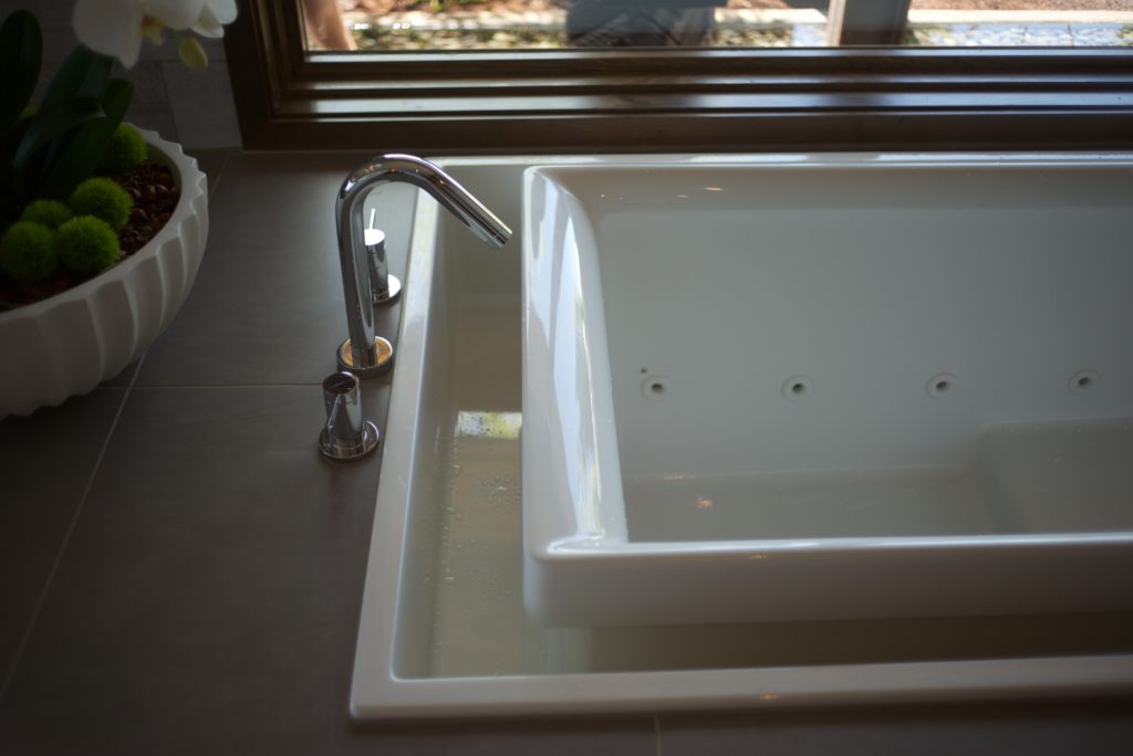 Infinity edge master bathtub fittings and fixtures