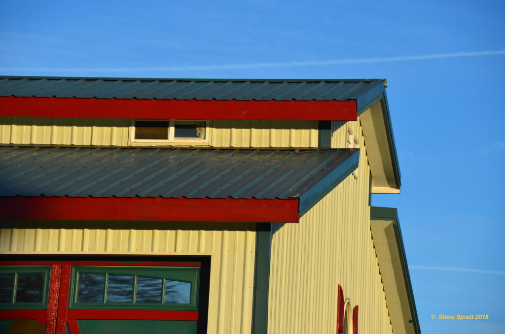Home exterior painted bright colors with metal roof and siding