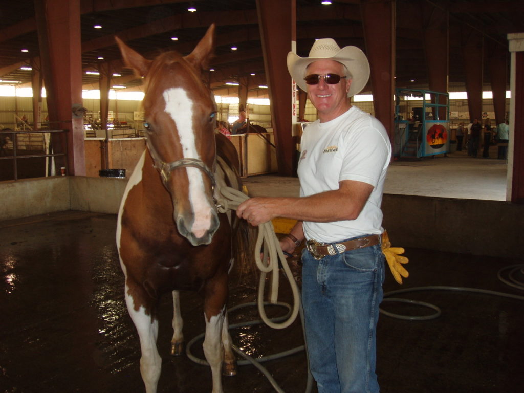 Image of Steve Spratt in jeans and cowboy hat with paint horse Sweets at home