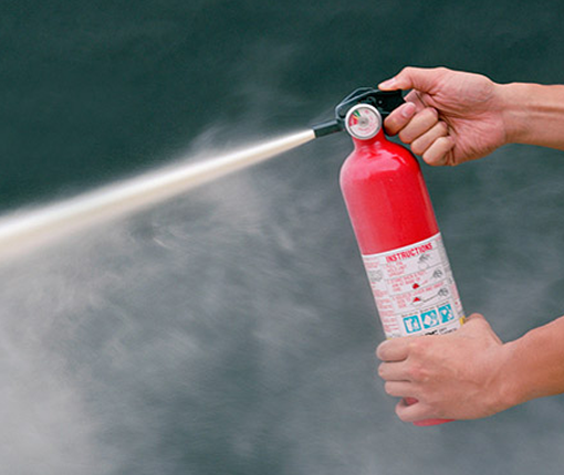 Image of hand held fire extinguisher in use