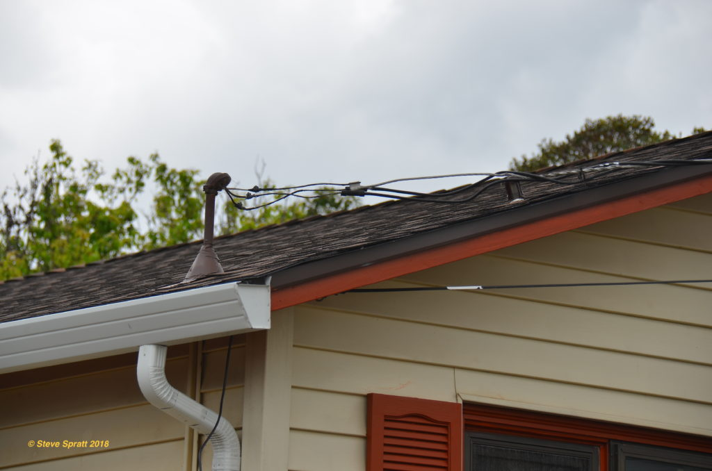 Image of old electrical service wires and mast on roof