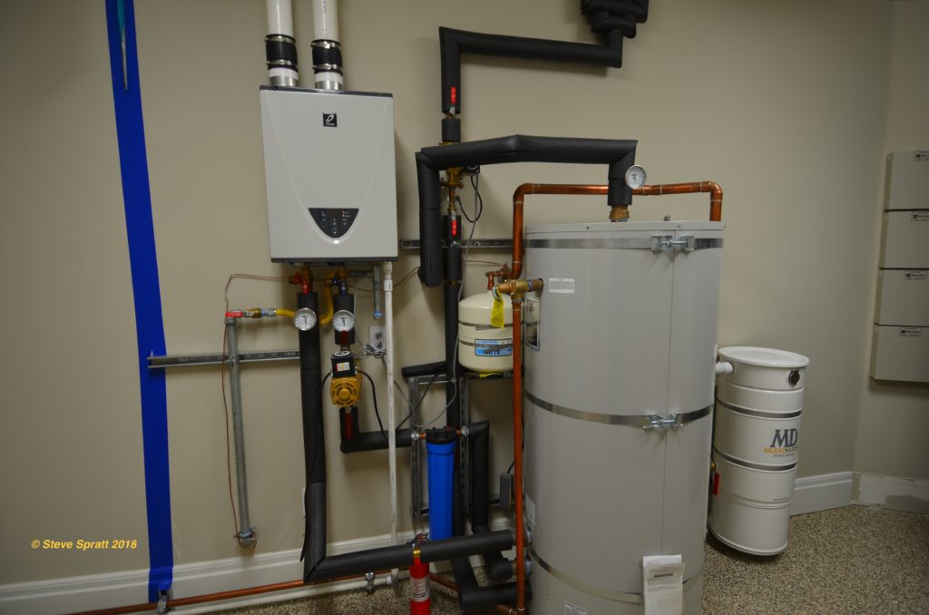 image of a demand water heater connected to a large storage tank plumbing system