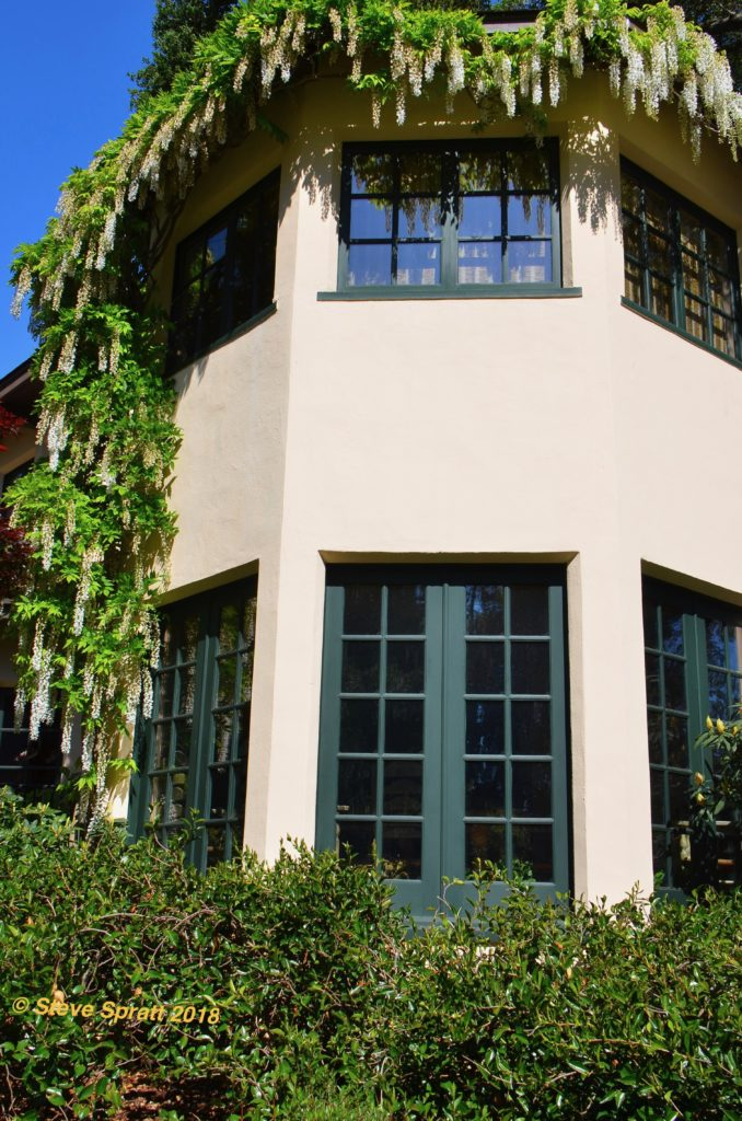 Image of two story home hexagon stucco sided turret with large windows