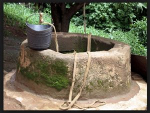 Photo of a hand dug potable water well with a bucket and rope for extraction