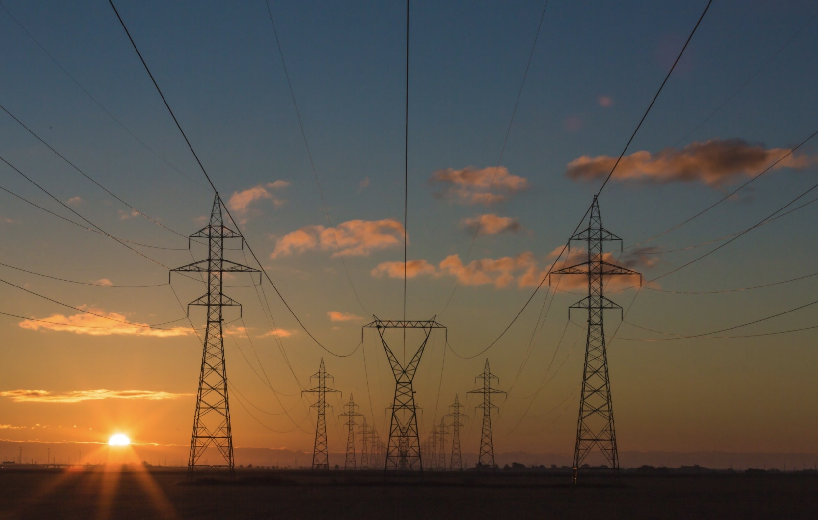 An image of overhead utilities, power lines and towers at sunset